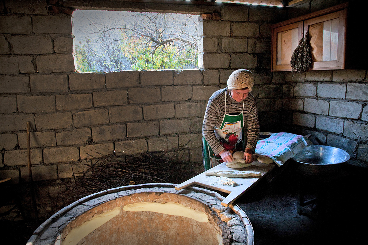 Vazha Nikolaishvili 's wife preparing traditional bread-which is baked in special clay oven over the coals which are prepared from burning of grapevine  branches.  Agro tourism farmhouse is run by  Vazha Nikolaishvili and his family.