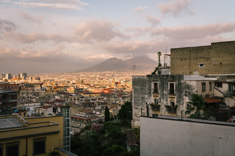 NAPLES, ITALY - 13 JULY 2019: A view of Mount Vesuvius is seen here from the terrace of the Osteria Totò Eduardo e Pasta e Fagioli, a restaurant in Naples, Italy, on July 13th 2019.<br /> The name of the Osteria is dedicated to the two masters of Neapolitan theatre and cinema: Totò (Antonio de Curtis) and Eduardo de Filippo. The idea came from Mario Bianchini, an aficionado of Neapolitan culture who wanted to pay tribute to his wife Rosaria de Curtis, a distant relative of Totò, the most famous actor in the history of Naples.<br /> The osteria was founded in the 1970s by Mario Bianchini who wanted to base its menu on traditional Neapolitan dishes. Mr Bianchini learned the art of cooking from his mother Anna.