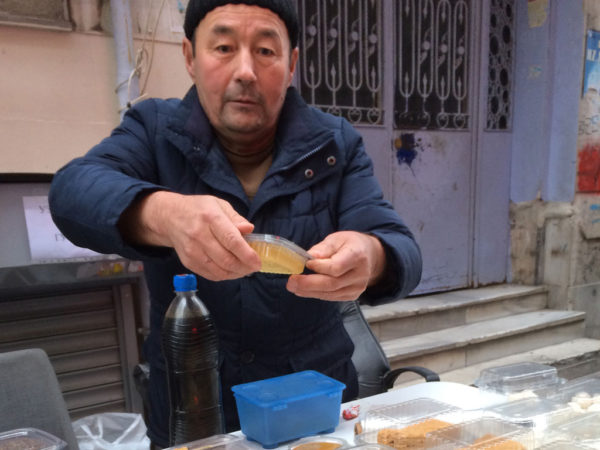 A migrant from Kyrgyzstan selling honey and herbs from the Naryn Oblast, photo by Ansel Mullins