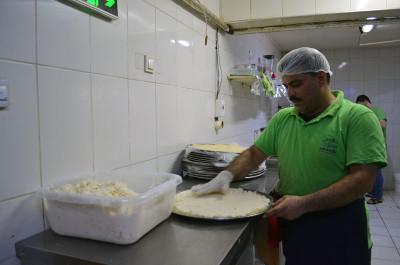 Ahmed spreads cream on a dessert at Salloura, photo by Dalia Mortada