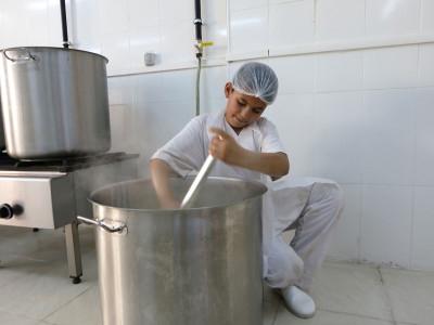 Rubi stirs milk for the ishta at Salloura, photo by Dalia Mortada