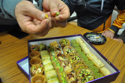 The group examining the sweets from Salloura, photo by Lauren Bohn
